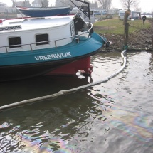 Er wordt een olie absorberend scherm aangelegt om de olie in de haven te houden