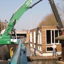 Een woonboot in de stad wordt voorzien van buispalen in een rollenbeugel