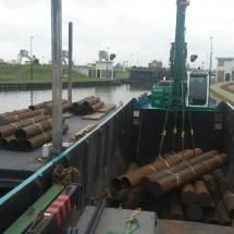 Ponton 3 geladen met stalen buizen voor een nieuwbouw project